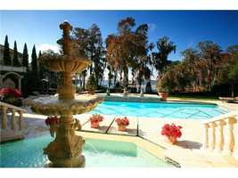 This view shows the fountain, pool, and nearby lake. Also the privacy and shade offered by multiple trees along the back perimeter of the property.