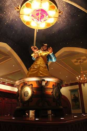 The rose gallery, adorned with rose accents, paintings and tapestries, is centered by a music box almost 7 feet tall with Belle and Beast twirling on top.
