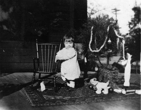 1912: A young child stands near a small Christmas tree surrounded by toys.