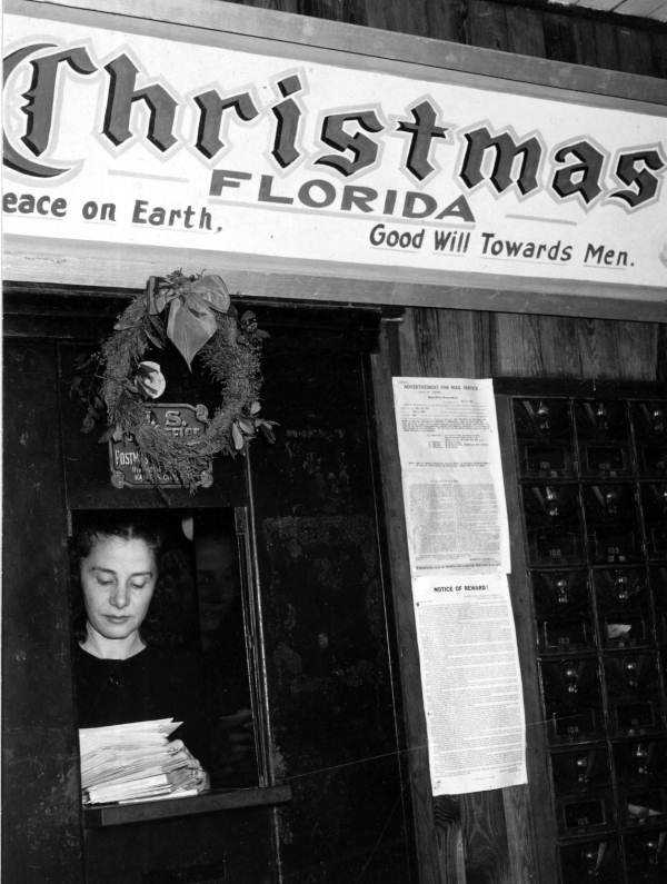 1947: A clerk at the Christmas, Florida post office sorts letters for Santa Claus.