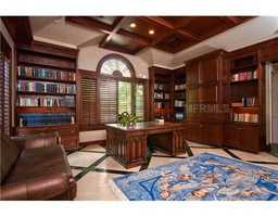 The study features custom wooden bookshelves and marble floors.