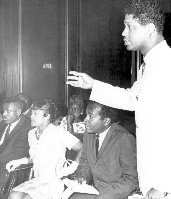Governor Burns hears complaints from black leaders. B.J. Johnson, far left, was representing Dr. Martin Luther King.