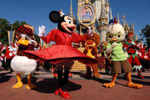 Minnie dances along in her all red dress during one of the holiday celebrations at the Disney parks.