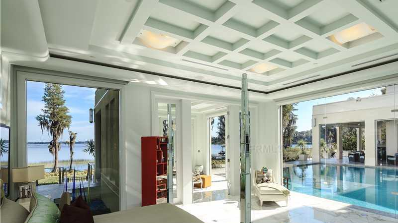 The master suite is on the first floor and has its own sitting area, glass garden, and floor to ceiling glass walls