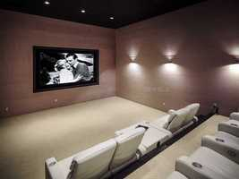 The home theater is situated and complete with beige suede walls, a Kaleidoscape media system, leather reclining chairs, and a theater lobby for picking up snacks.