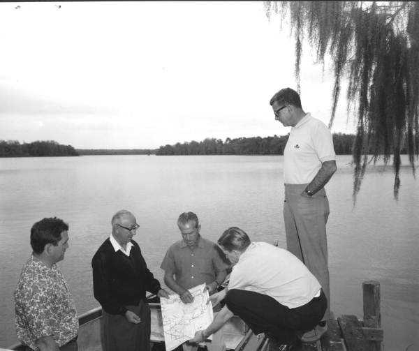 Roy Disney and others inspect a map.