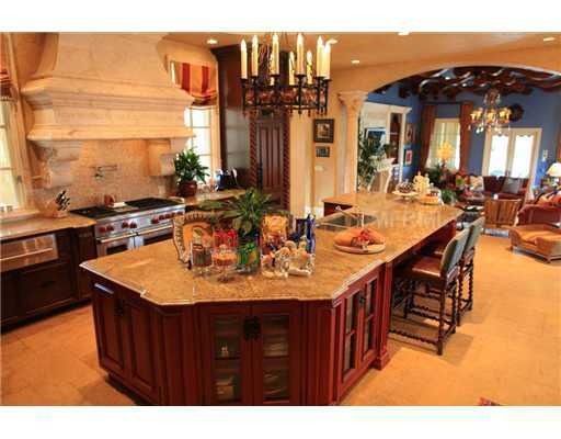 Spacious kitchen features a large, marble-topped island and dining bar for four.