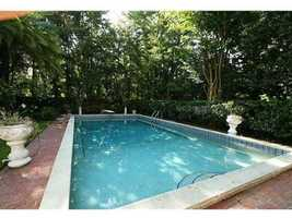 The property has its own private pool, surrounded by lush plants.
