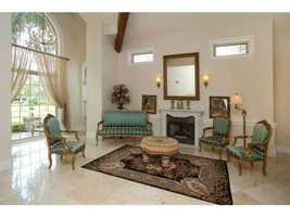 A formal sitting area features a large window overlooking the property and its own fireplace.