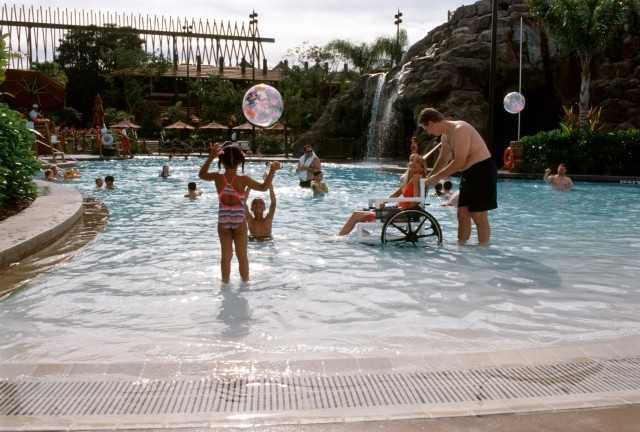 "Guests at Disney's Polynesian Resort now enjoy the pool with the ""zero-entry"" feature. Resembling a beachfront shoreline, the architectural feature offers guests a gradual ramp into the water. Guests with disabilities are invited to use special wheelchairs provided by the resort to help them enjoy the pool."
