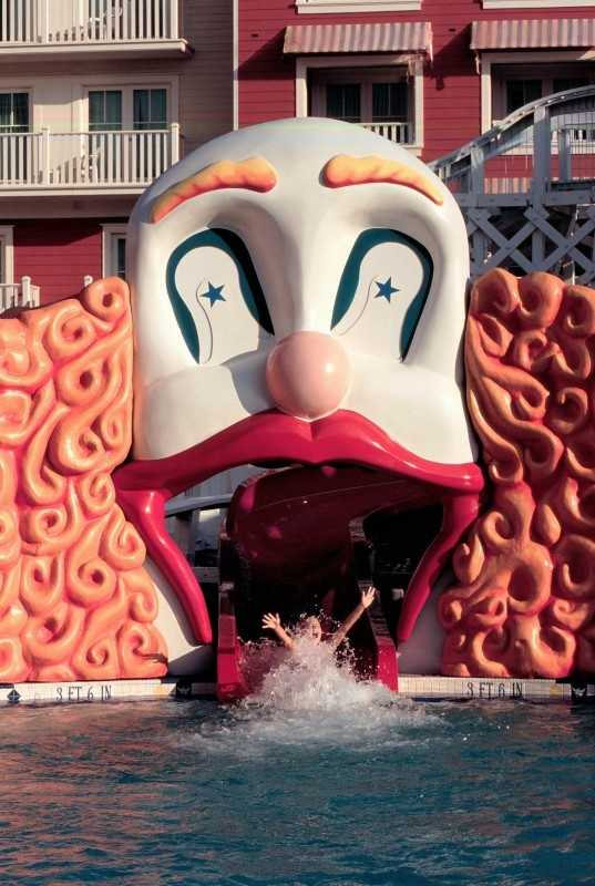 A clown-faced roller coaster water slide propels guests of all ages into Luna Park -- the carnival-themed swimming pool at Disney's BoardWalk Resort.  The resort's pool area also features a whimsical carousel pool bar and a herd of playful elephant statues spraying water from their trunks.
