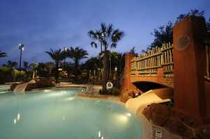Swaying palm trees and azure waters combine with the thrills of a 128-foot water slide at Samawati Springs Pool at Kidani Village. The themed feature pool is a zero-depth entry pool with fun-filled water slide and two whirlpool spas. The property is located at Disney's Animal Kingdom Lodge.