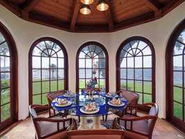 The dining nook is surrounded by arched windows overlooking Lake Tibet and the backyard.