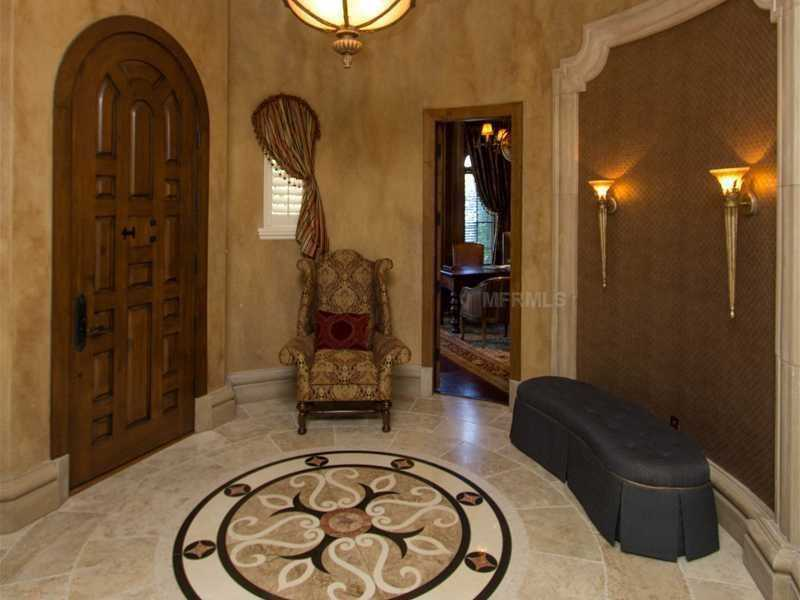 The foyer features a hand-carved entry door and inland marble.