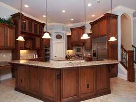 The gourmet kitchen has a large center island with a vegetable sink, granite counters, oversized breakfast bar, G.E. Monogram stainless appliances.