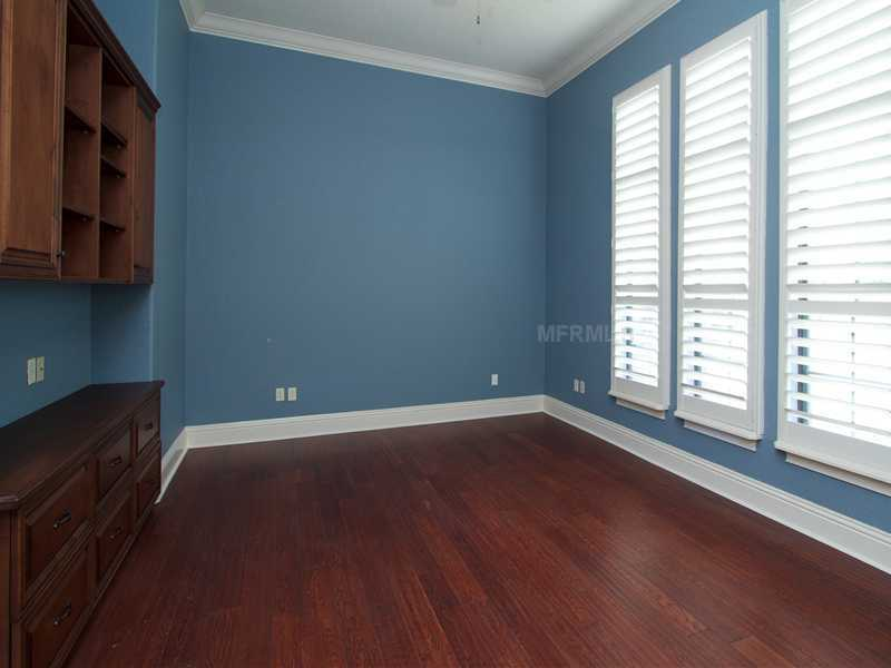 The guest bedroom has custom shelving and hardwood floors.