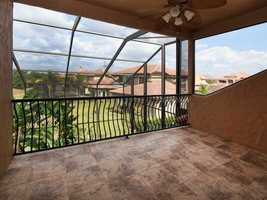 The balcony overlooks the enclosed pool and is has marble floors.