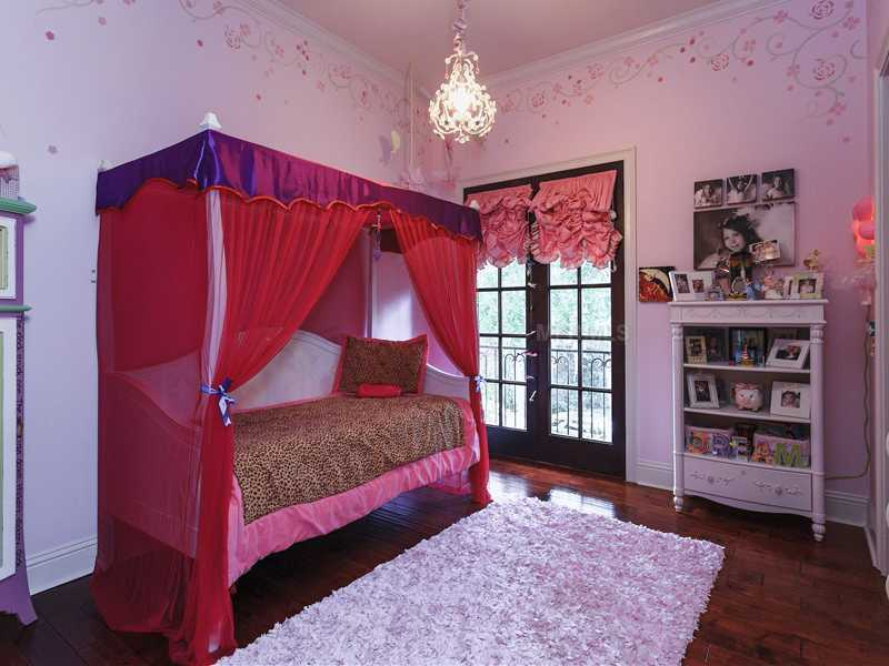 This charming girl's room features a canopy daybed and princess chandelier.