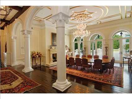 The formal dining room starts with the same Brazilian walnut flooring and Roman pillars. But the focal point of this dining room is the crystal chandelier.