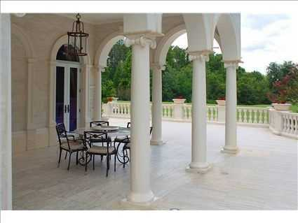 This covered porch overlooks the impeccably manicured lawn.