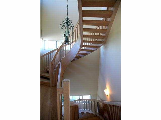 Winding, wooden staircase spirals up to the third floor.