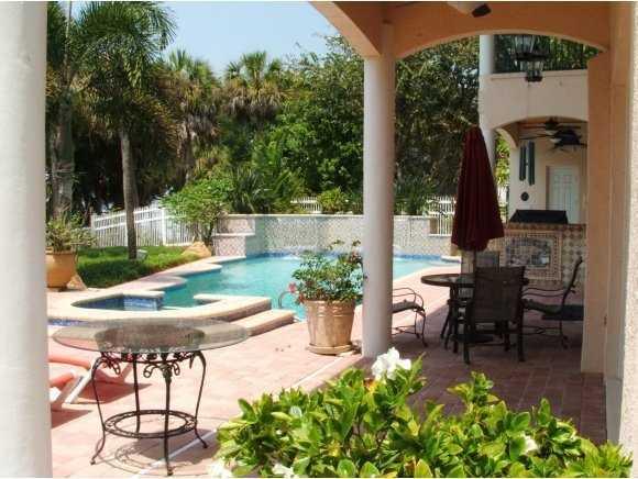 The patio, which is covered by cypress wood ceilings, includes a beautiful pool and outdoor spa.