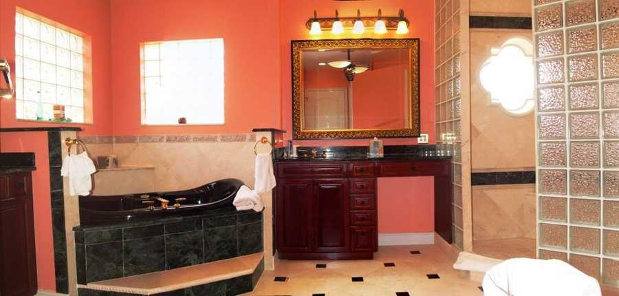 Master bathroom features a grand spa tub and his and her vanity areas.
