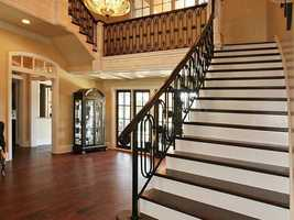 Elegant staircase is illuminated by a charming chandelier above the foyer.