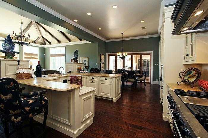 This view shows off the spacious kitchen. Looking over the counter-tops and under the exposed wooden beams, you will find an unbelievable family room.