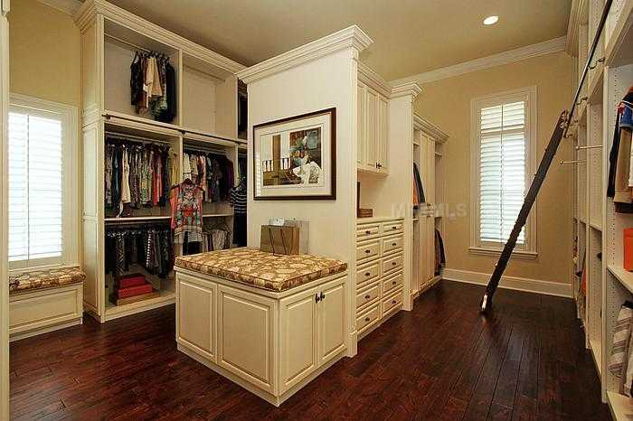 Closet features mirrored dressing closets, library ladder, storage & packing bench & washer/dryer!