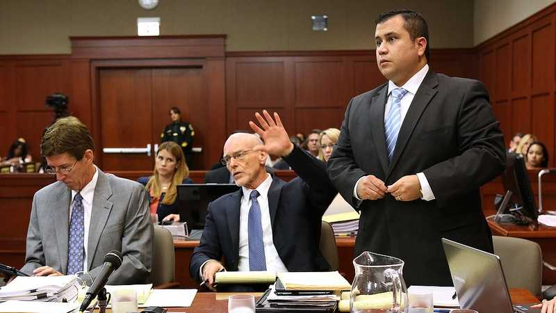 George Zimmerman, with his attorneys, Mark O'Mara (left), and Don West, stands to be identified by state witness Chris Serino, a Sanford police officer, during his testimony in Zimmerman's trial in Seminole circuit court, in Sanford, Fla., Monday, July 1, 2013. West is signaling to the witness that his client will stand to be identified. (Joe Burbank/Orlando Sentinel/POOL)