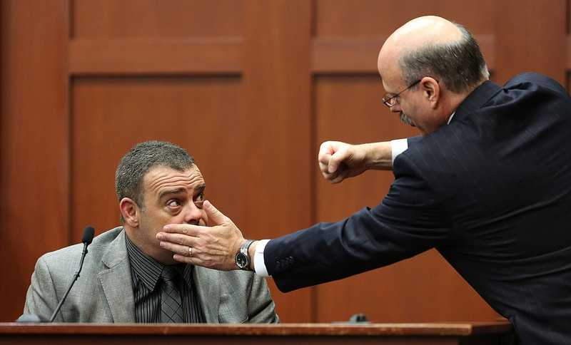 Prosecutor Bernie de la Rionda demonstrates a possible scenario while questioning state witness Chris Serino, a Sanford police officer, during the George Zimmerman trial in Seminole circuit court, in Sanford, Fla., Tuesday, July 2, 2013. Zimmerman is charged with 2nd-degree murder in the fatal shooting of Trayvon Martin, an unarmed teen, in 2012. (Joe Burbank/Orlando Sentinel/POOL)