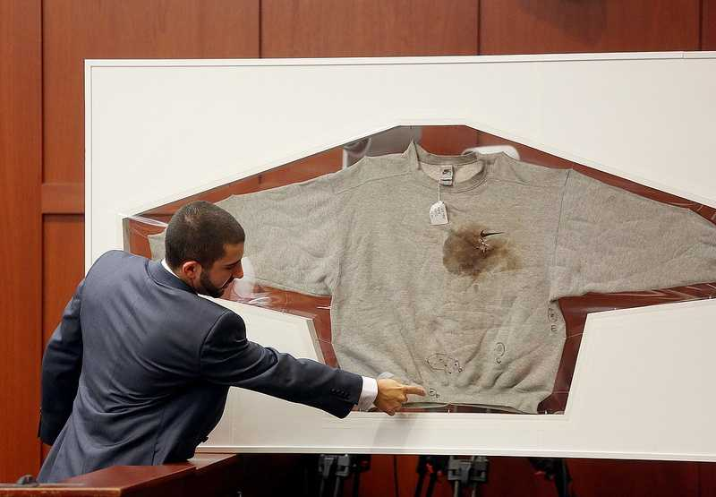 FDLE Crime Lab Analyst Anthony Gorgone points to a sweatshirt worn by Trayvon Martin on the night Martin was shot during the George Zimmerman trial in Seminole circuit court, in Sanford, Fla., Wednesday, July 3, 2013. Zimmerman is charged with 2nd-degree murder in the fatal shooting of Trayvon Martin, an unarmed teen, in 2012. (Jacob LangstonOrlando Sentinel/POOL)