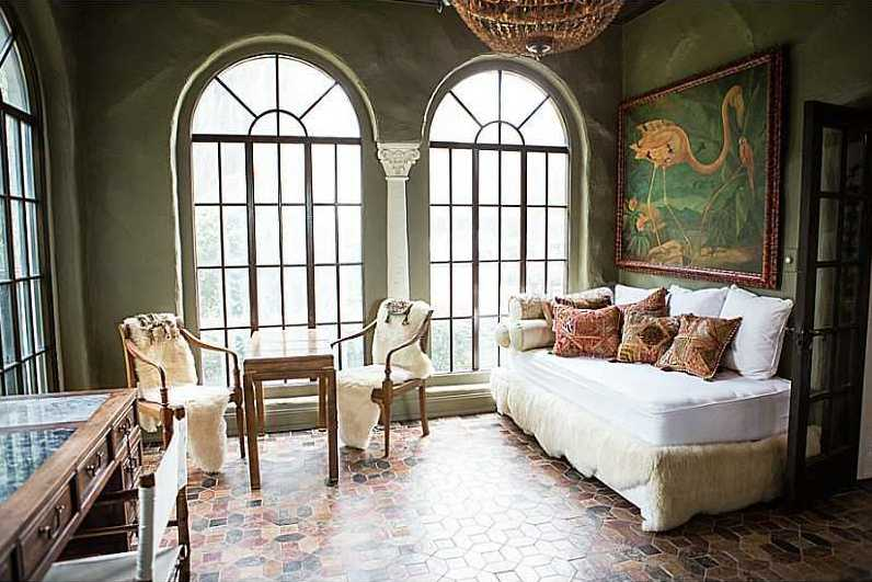 Floor-to-ceiling arch windows on each wall of this beautiful office. The original tile is complemented by the tropical wall art and vintage chandelier.