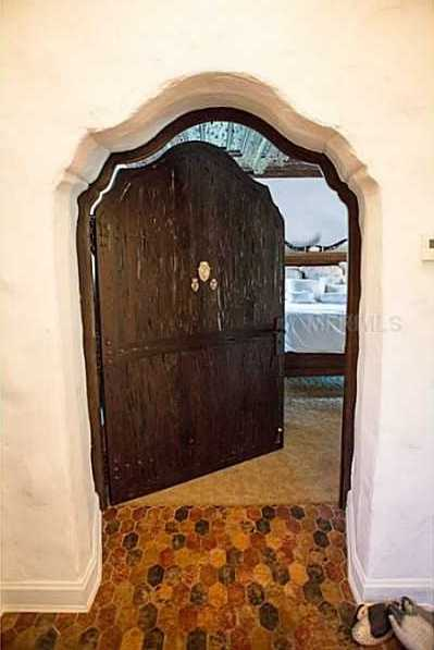 Rustic, uniquely arched doors lead to the master suite.