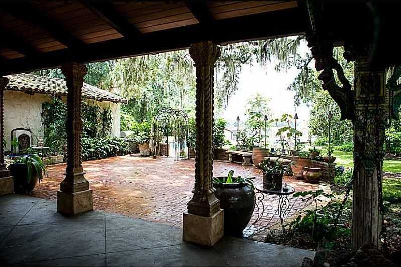 The tiled porch is surrounded by lush trees and plants.