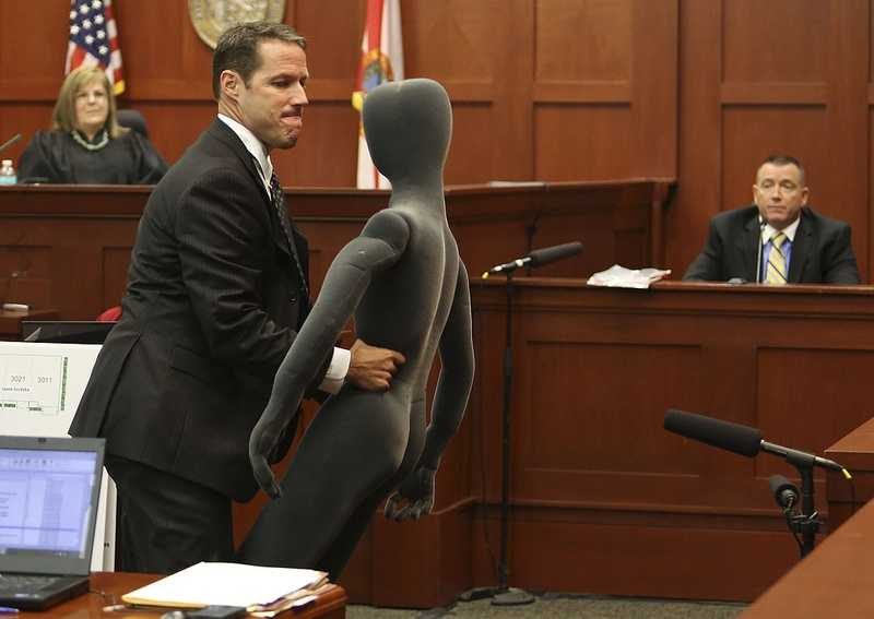 Assistant state attorney John Guy uses a foam dummy to describe and demonstrate the altercation between George Zimmerman and Trayvon Martin to defense witness and law enforcement expert Dennis Root during Zimmerman's trial in Seminole circuit court in Sanford, Fla. Wednesday, July 10, 2013. Zimmerman has been charged with second-degree murder for the 2012 shooting death of Trayvon Martin. (Gary W. Green/Orlando Sentinel)