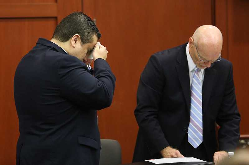 George Zimmerman's wife, Shellie, watches her husband arrive in the courtroom on the 24th day of his trial at the Seminole County Criminal Justice Center, in Sanford, Fla., Friday, July 12, 2013. In the foreground, Zimmerman's parents, father Robert Zimmerman, Sr., and mother Gladys Zimmerman. Zimmerman is charged with 2nd-degree murder in the fatal shooting of Trayvon Martin, an unarmed teen, in 2012. (Joe Burbank/Orlando Sentinel/POOL)