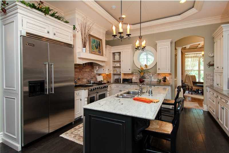 Exposed brick behind the gas stove adds texture to this gourmet kitchen, which also features a center island, top of the line appliances, and built in custom table.