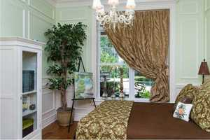 One of six bedrooms, it includes custom wall moldings and chandelier.