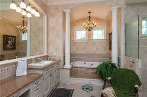 Beautiful master bathroom features an elegant space for the jacuzzi tub.