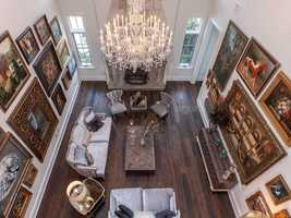Antique art displayed on the soaring walls add drama and elegance to the room. It also includes hardwood floors, which are featured throughout the home.