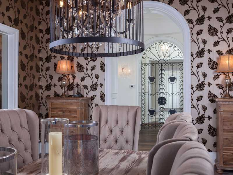 The dining room features plush seating, vine covered wallpaper, and an iron-caged chandelier.