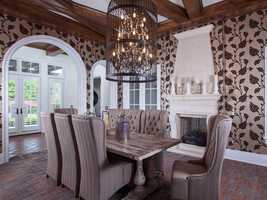 This alternate view of the dining room reveals the beamed ceilings, brick floors and access to the outdoor patio.