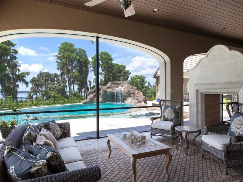 A luxurious patio setting overlooks the massive pool and private lake dock.