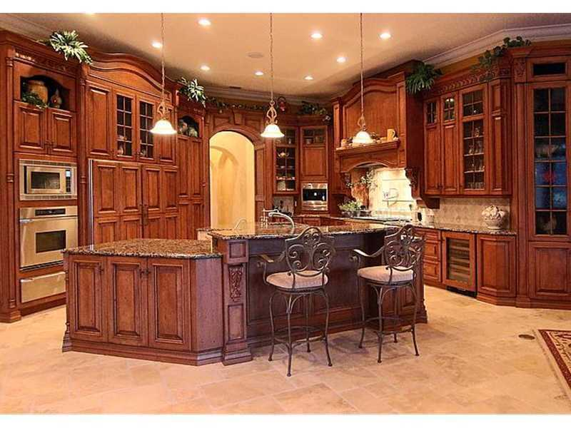 Custom cabinetry in the expansive ground floor kitchen, complete with granite counter tops, gourmet appliances, and spacious bar seating.