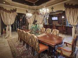 The formal dining room is draped in elegance, and it's steps away from an expansive wine rack and adjoining bar.