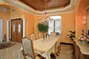 Custom hand-painted faux ceilings compliment the coffered ceilings in all rooms, including this elegant dining room. All of the rooms on the first floor have 12 foot ceilings.