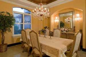 An exquisite chandelier is the focal piece of this dining room. In addition, the floors also boast imported Indian granite. This granite is also used on the counters, floors, grand stairway and custom one-of-a-kind entertainment centers in the family room.