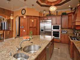 The gourmet kitchen includes high-end cabinetry, gas appliances, a massive 8 foot island and a hidden walk-in pantry.
